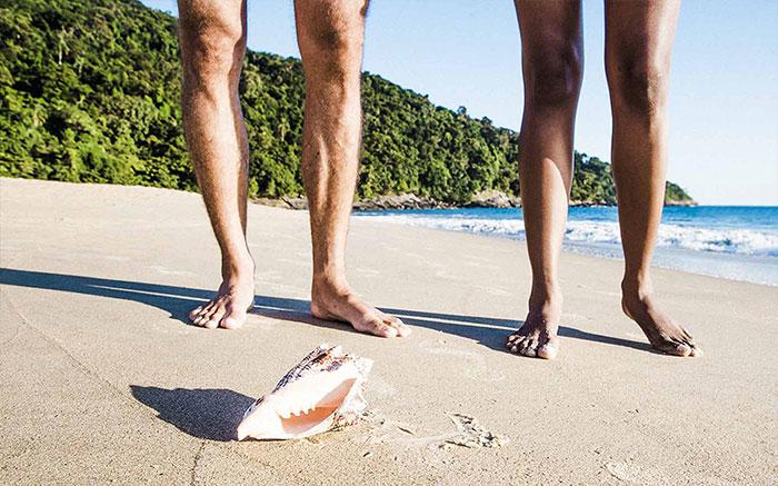 Primo piano della gambe di due persone su una spiaggia tropicale