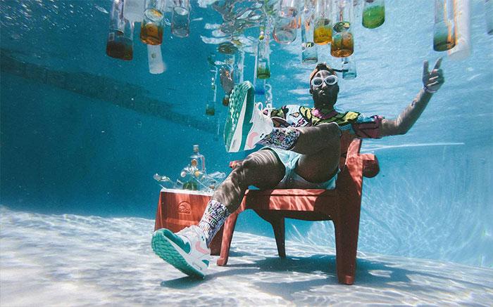 Un ragazzo seduto sul fondo di una piscina circondato da bottiglie